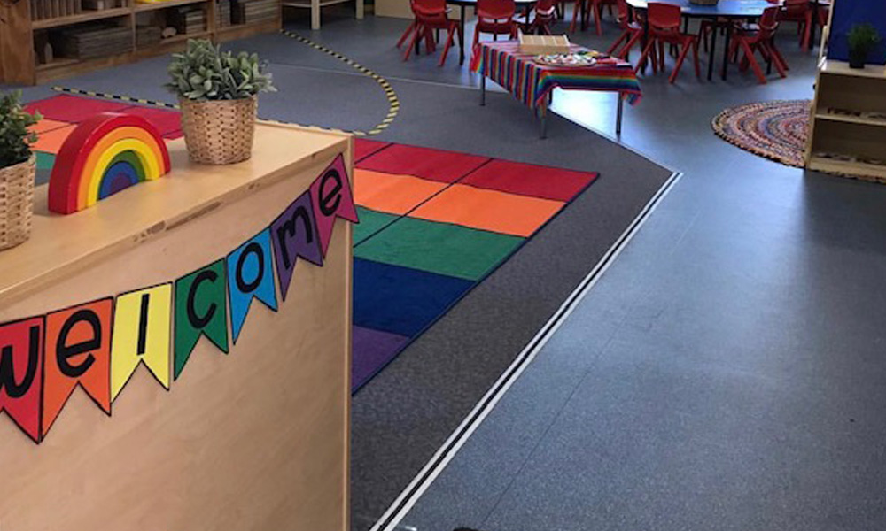 primary school classroom with welcome banner and colourful rug