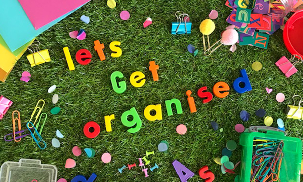Lets get organised magnetic letters on grass background surrounded by teaching resources