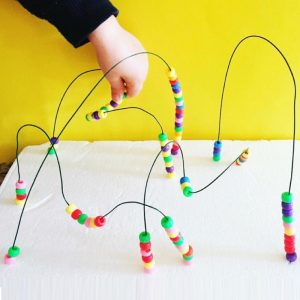 Bead Maze Multi-Coloured Beads On Looped Wire With Yellow Wall Background