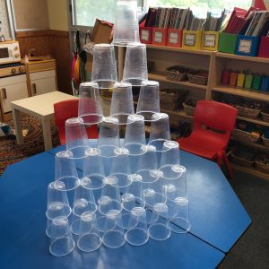 Cup Tower On Table Clear Cups Multilevel Tower On Blue Desktop