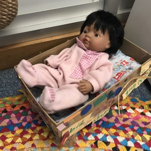 Doll Bed With Black Doll Inside Sitting On Bright Multicoloured Rug