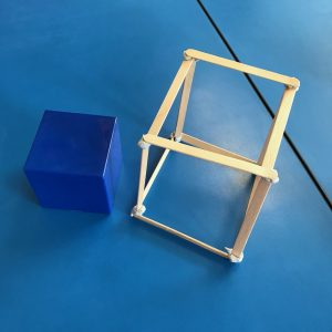 Paddle Pop Stick Cube With Smaller Blue Cube Sitting On Blue Desktop