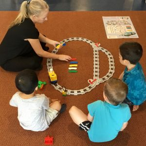 Coding Express Activity Three Children With Teacher Setting Up Track On Floor