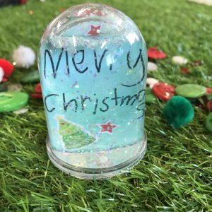 Snow Globe Merry Christmas With Buttons Sitting On Grass