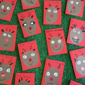 Rudolf Christmas Cards Displayed Singly Spread Out On Green Grass