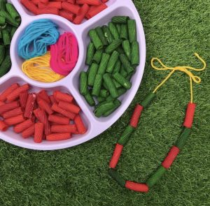 Christmas Pasta Necklace Activity With Coloured Pasta On Grass