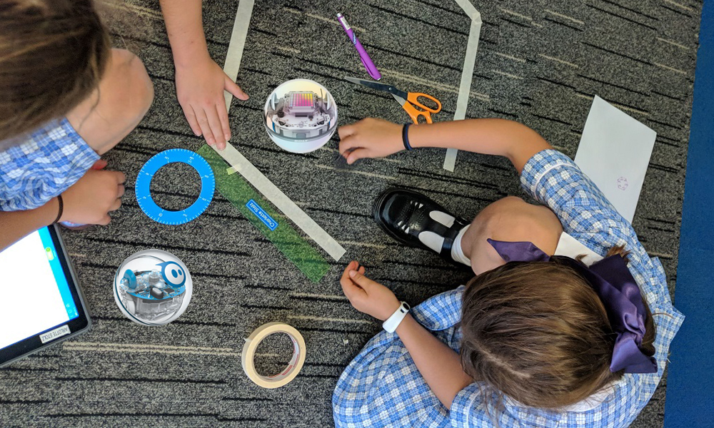 Sphero Shape Activity birds eye view featuring Sphero Bolt & SPRK robotics and 2 students on carpet.